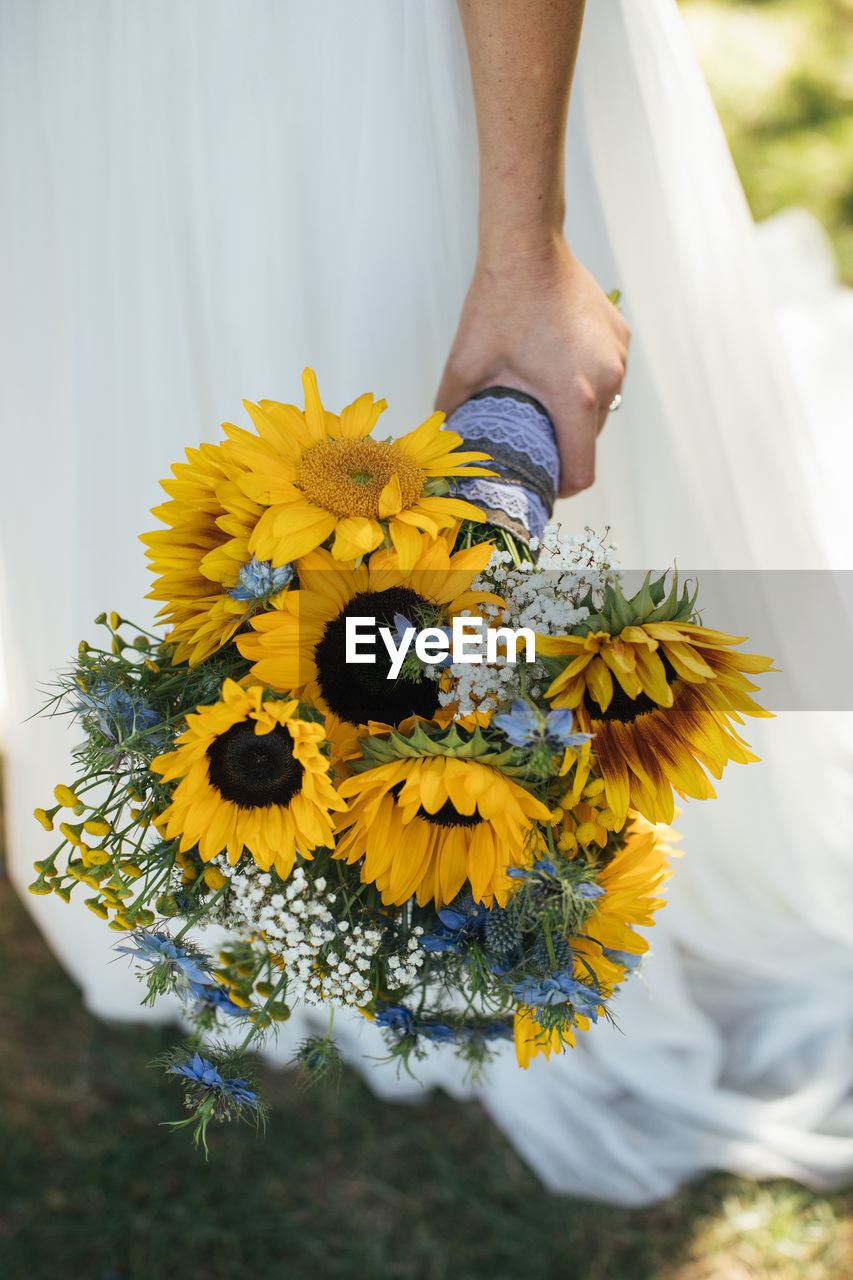 flower, flowering plant, one person, freshness, yellow, plant, fragility, vulnerability, real people, beauty in nature, human body part, hand, nature, growth, human hand, flower head, holding, close-up, day, body part, outdoors, flower arrangement, bouquet, human limb, finger