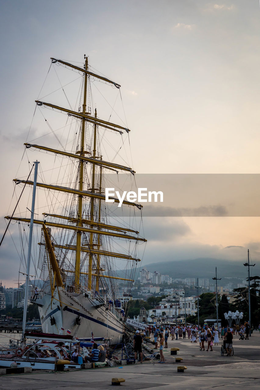 nautical vessel, transportation, sky, mode of transport, outdoors, mast, real people, sunset, cloud - sky, sea, day, nature, moored, large group of people, harbor, water, architecture, people