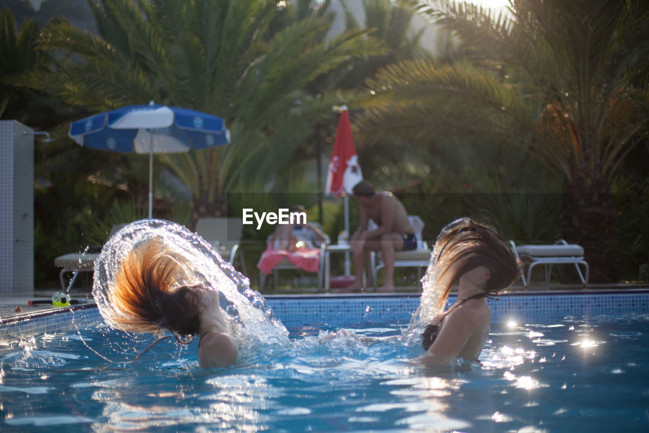 swimming pool, water, leisure activity, real people, enjoyment, lifestyles, fun, swimming, togetherness, vacations, outdoors, water park, day, happiness, headshot, weekend activities, friendship, summer, two people, childhood, young women, women, water slide, palm tree, young adult, tree, people