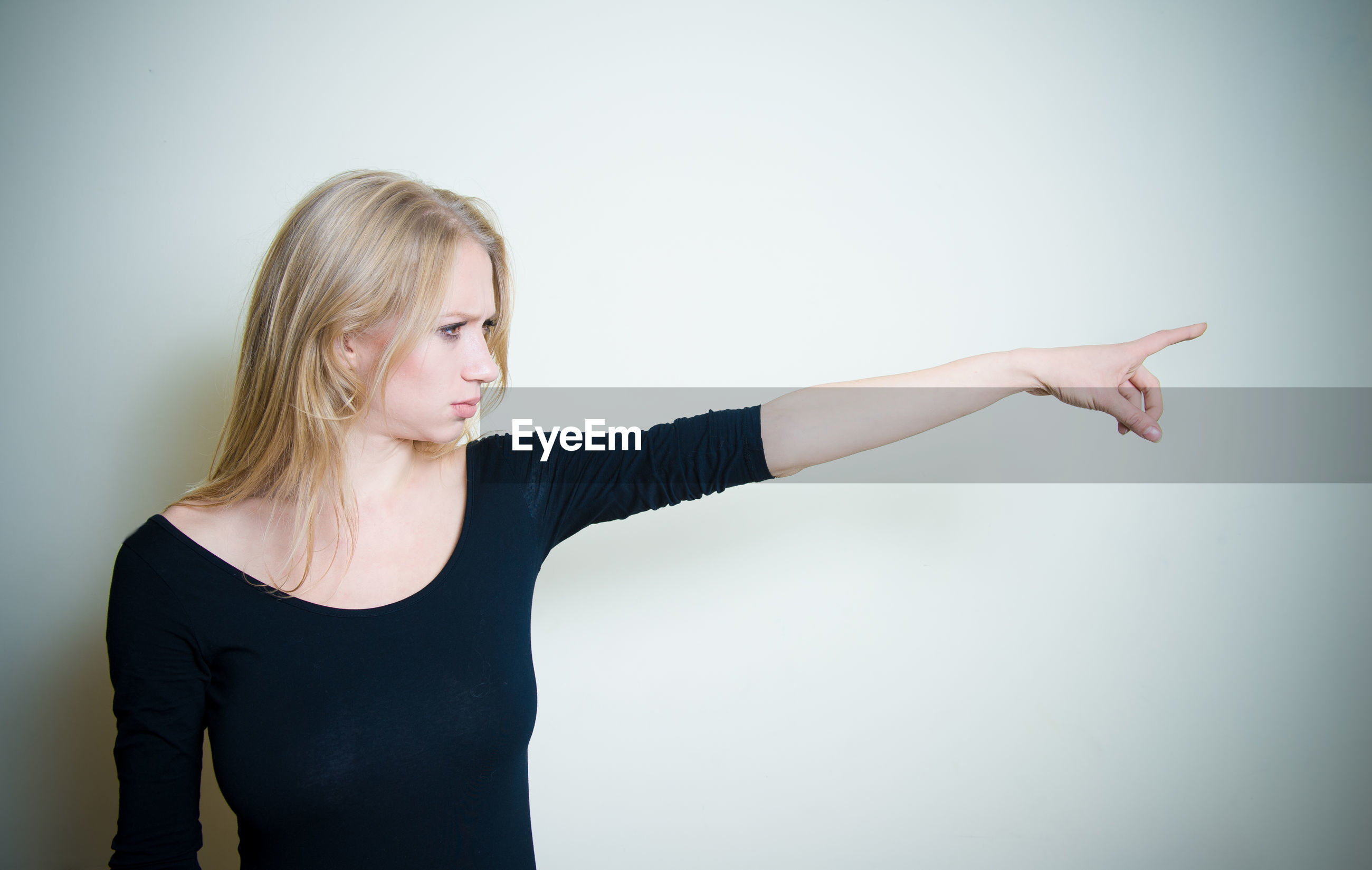 Young woman pointing away against white background