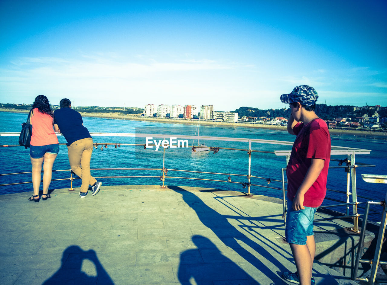 real people, lifestyles, railing, day, leisure activity, two people, full length, water, outdoors, built structure, sunlight, sky, architecture, sea, city, standing, women, men, young adult, young women, cityscape, people