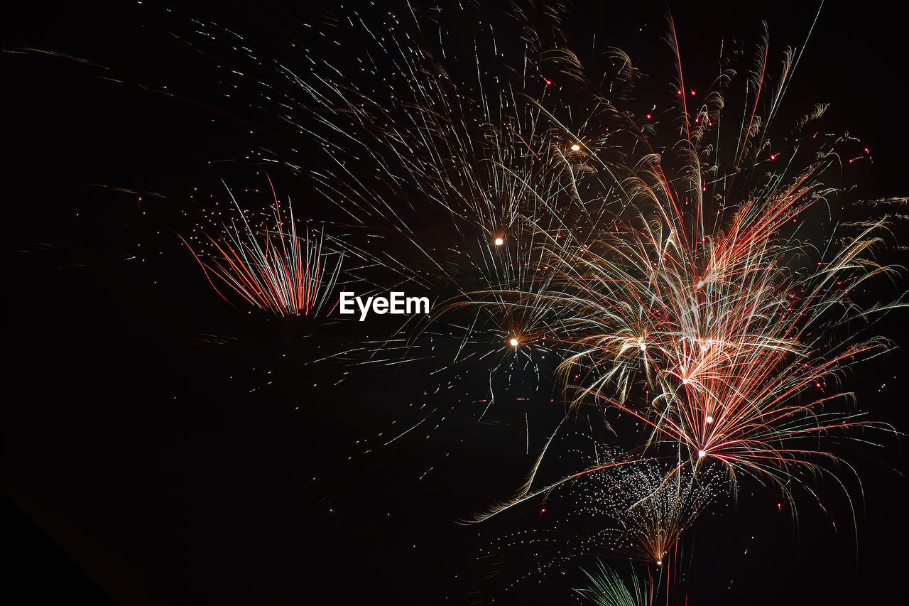 night, firework display, celebration, firework - man made object, exploding, long exposure, sparks, glowing, arts culture and entertainment, motion, event, illuminated, low angle view, no people, blurred motion, firework, multi colored, outdoors, sky