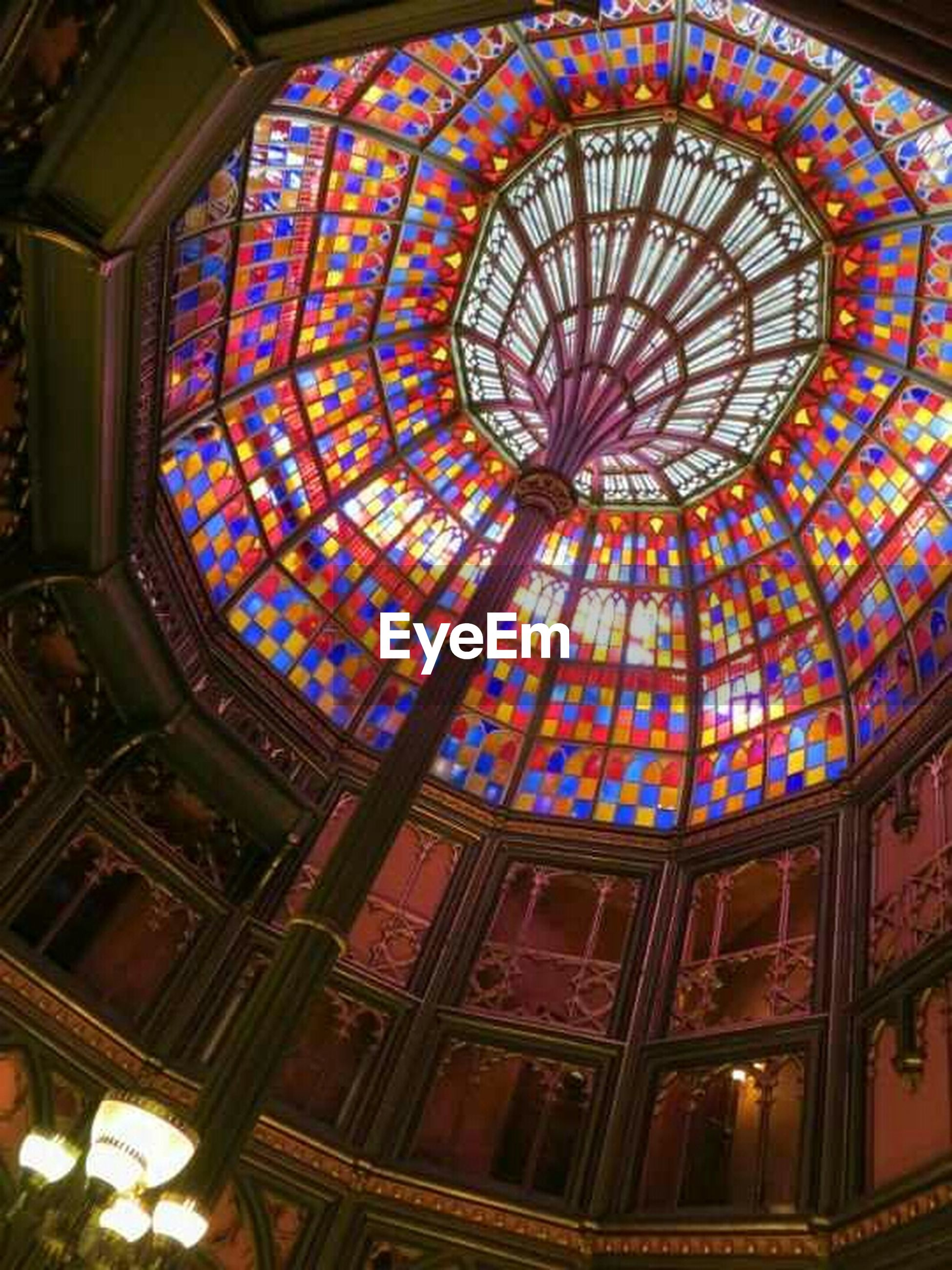 indoors, low angle view, ceiling, architecture, built structure, place of worship, design, religion, ornate, spirituality, pattern, church, stained glass, architectural feature, art and craft, art, dome, window, skylight