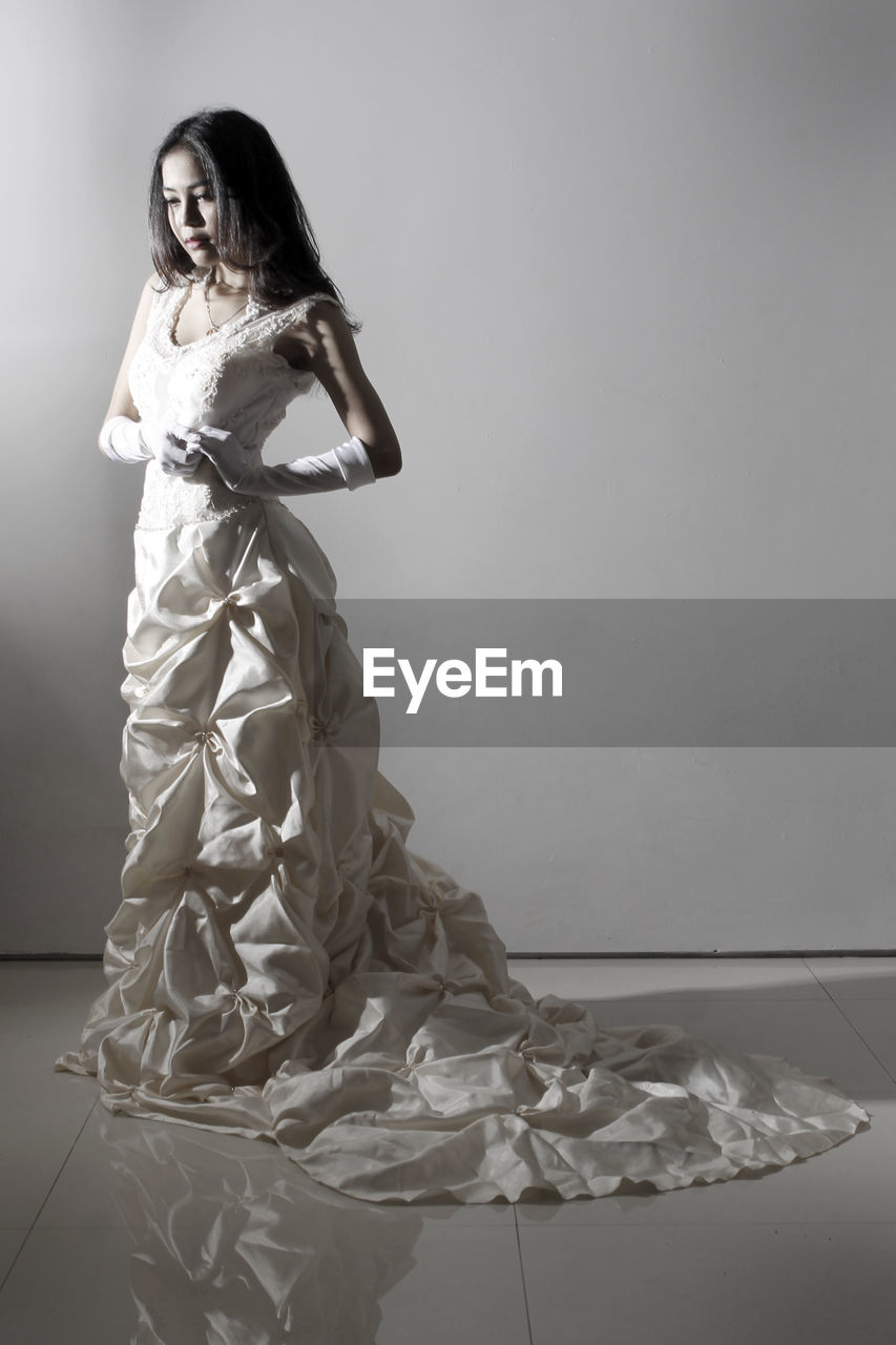 Bride standing against gray background