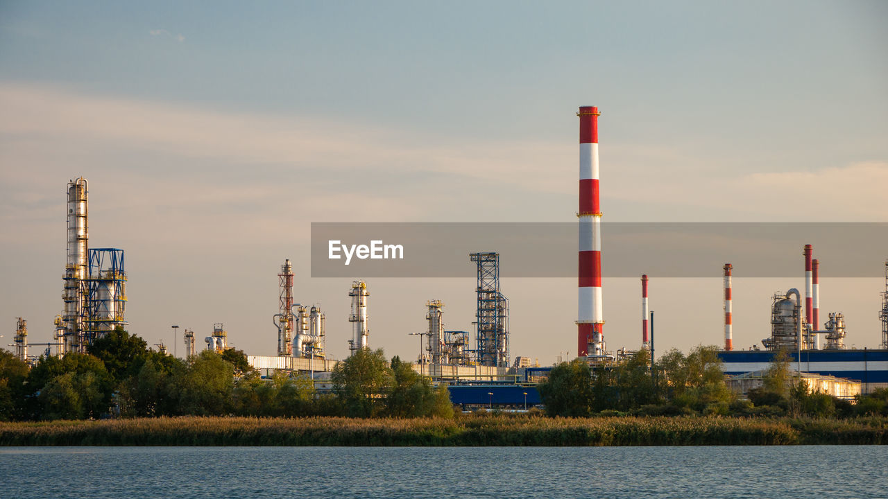 sky, industry, fuel and power generation, factory, built structure, architecture, nature, water, building exterior, oil industry, outdoors, waterfront, no people, technology, day, fossil fuel, refinery, tower, environmental issues