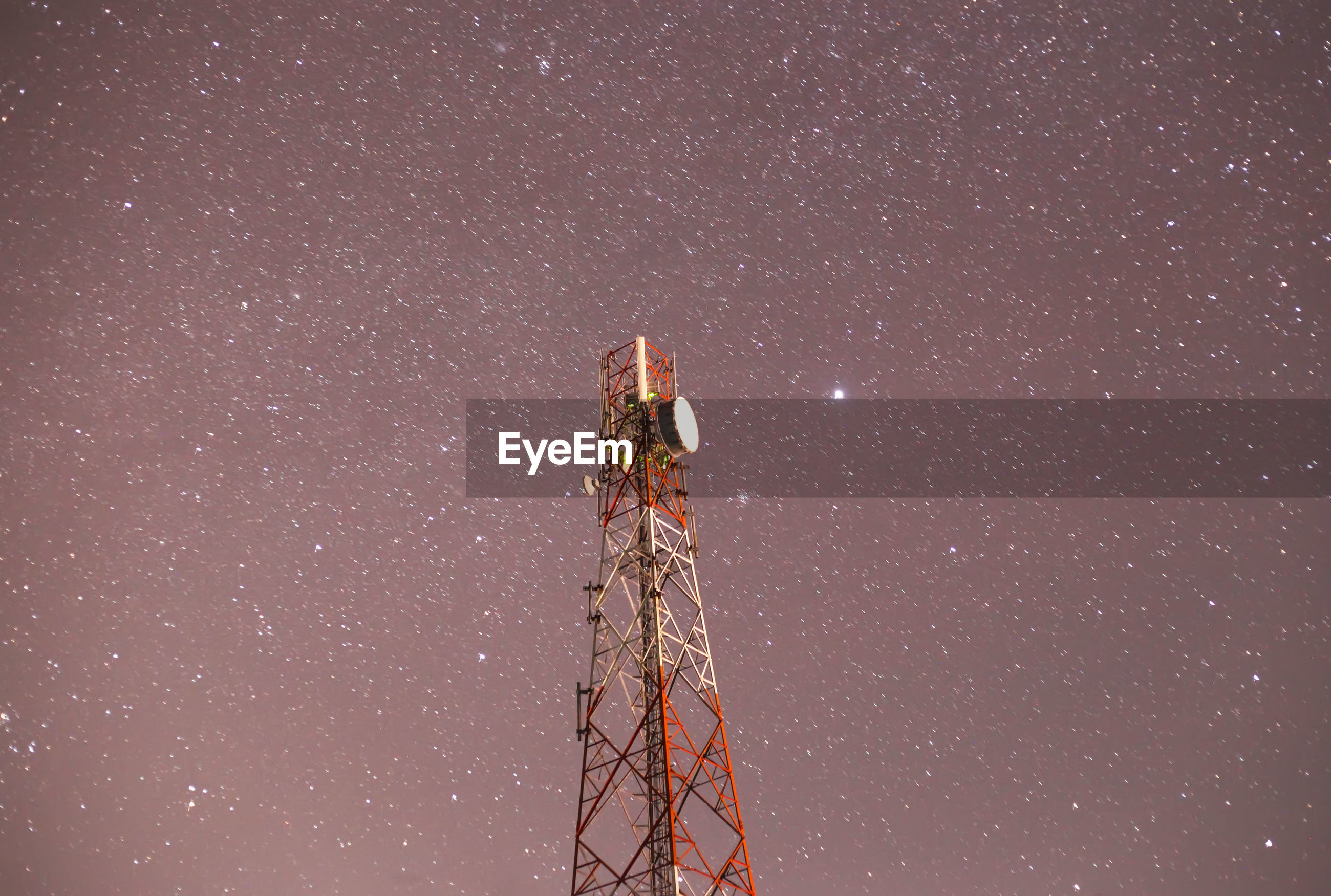 Low angle view of illuminated communications tower against sky at night