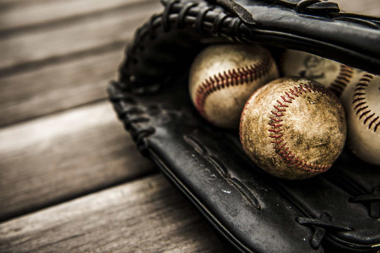 Close-up of baseball gloves and baseballs on wooden table
