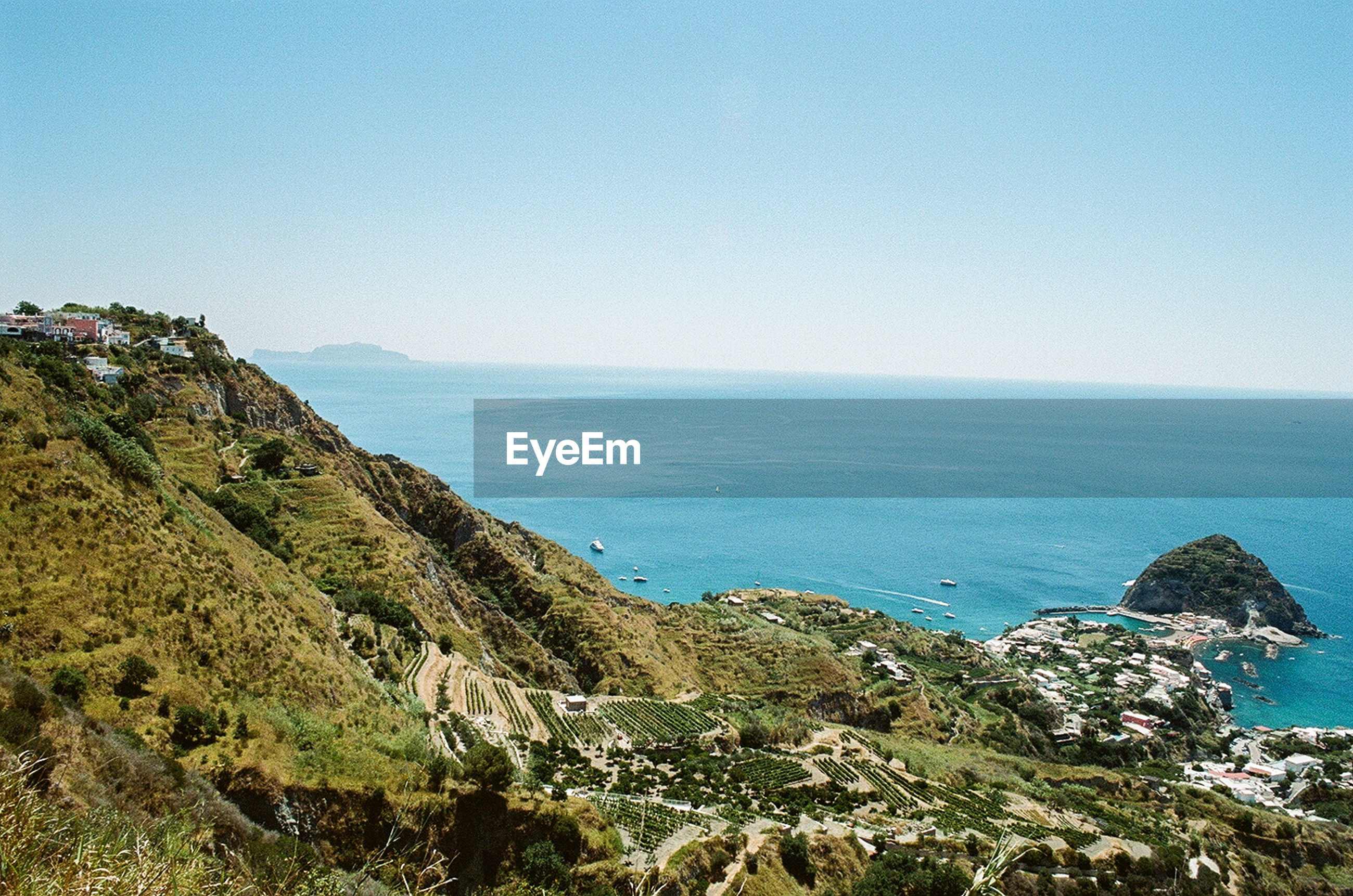 Scenic view of mountain by sea against clear blue sky