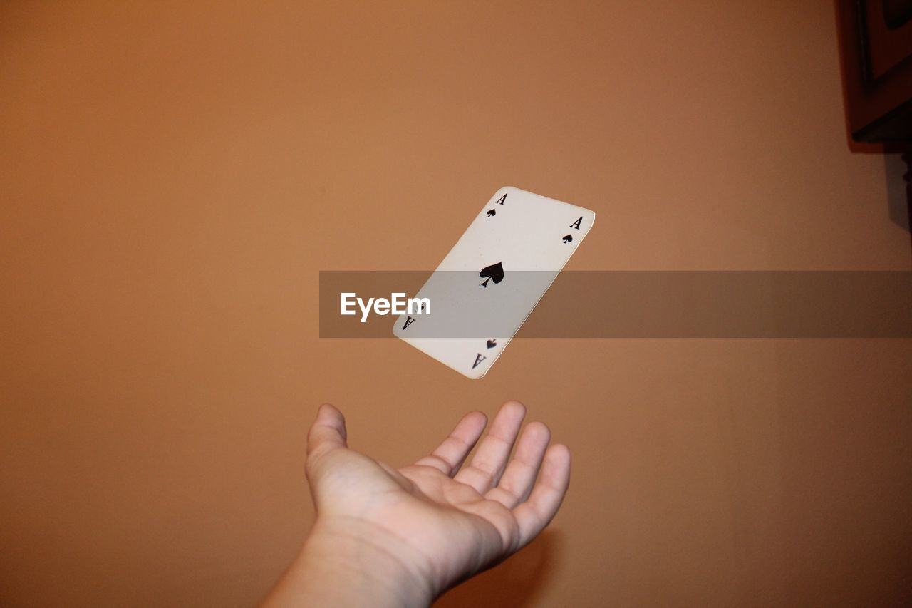 Cropped Hand Catching Card Against Wall