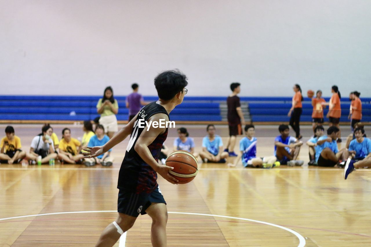 Young man with basketball in school gymnasium