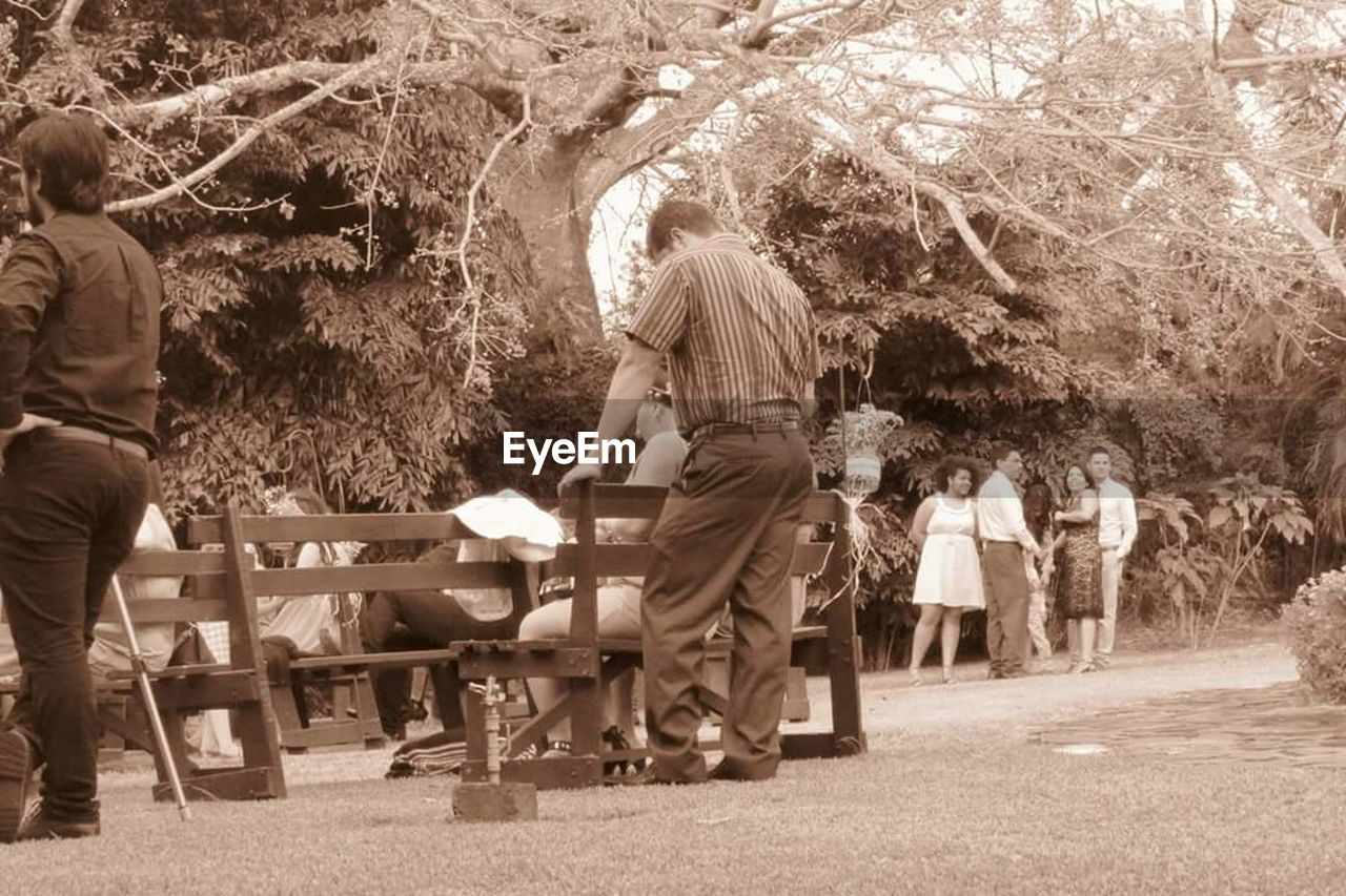 togetherness, adult, table, senior adult, tree, boys, outdoors, people, men, full length, day, childhood, standing, child, nature, young adult