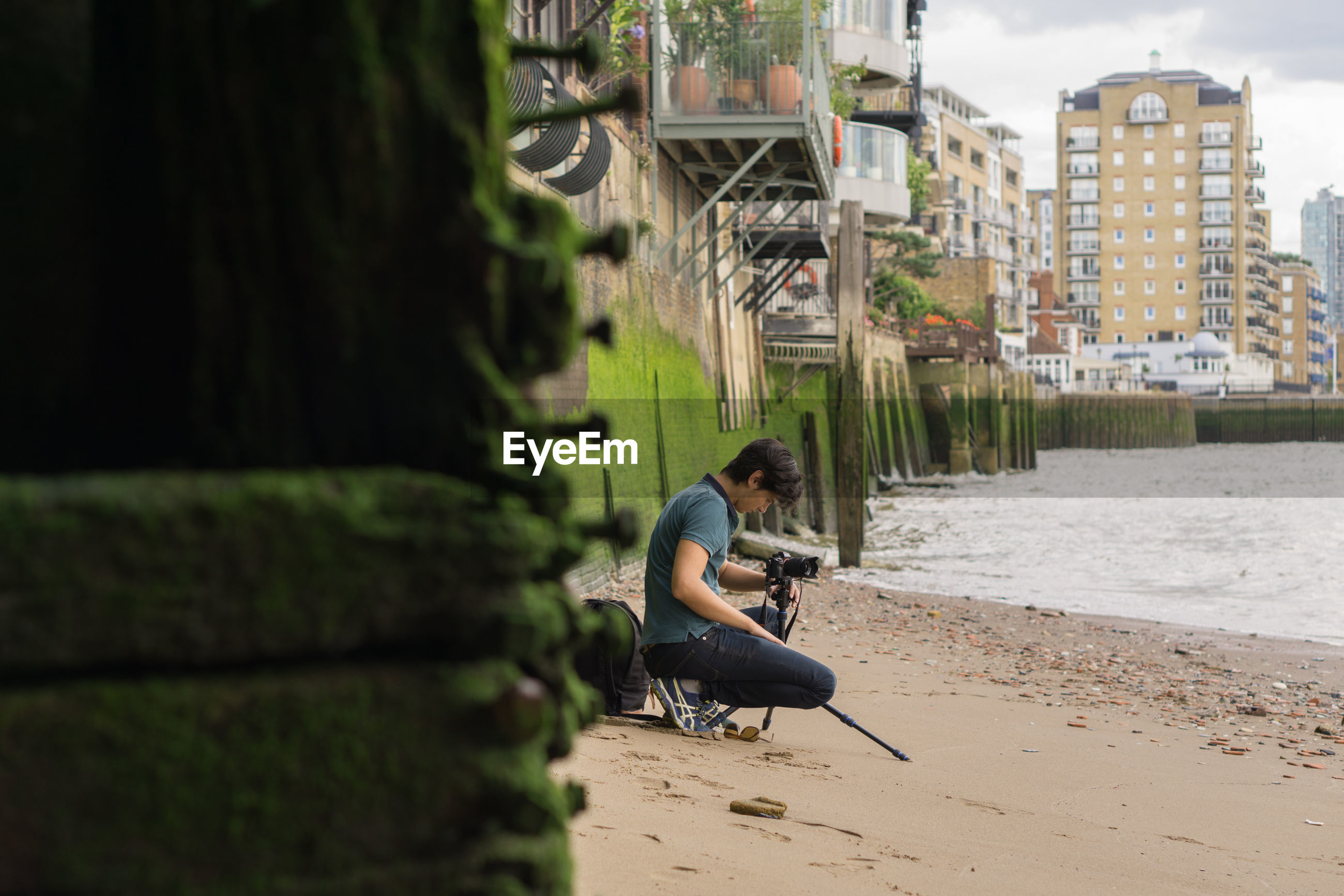 Side view of man photographing at beach