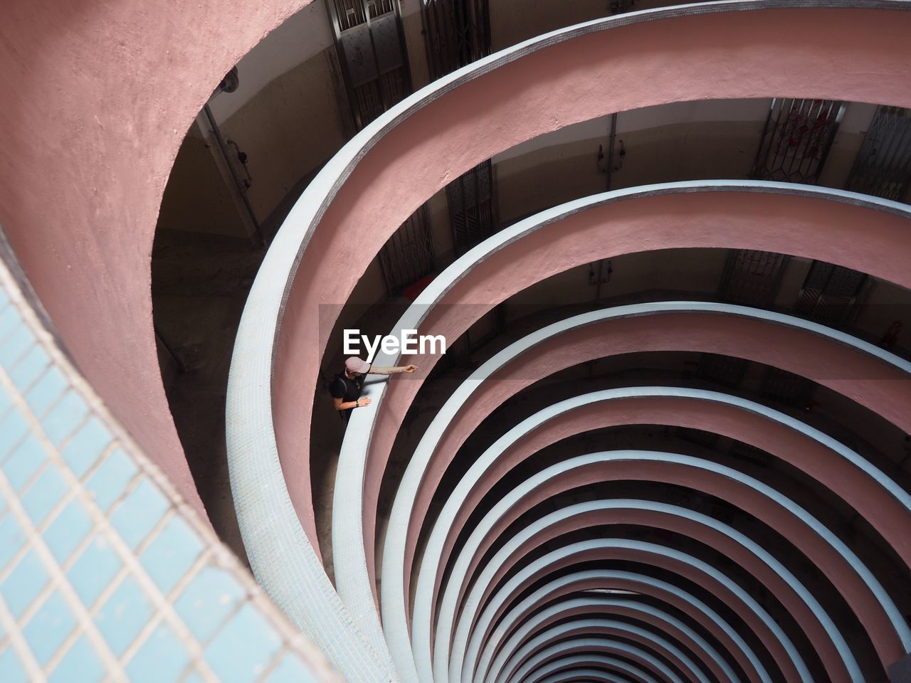 High Angle View Of Man Standing In Spiral Building