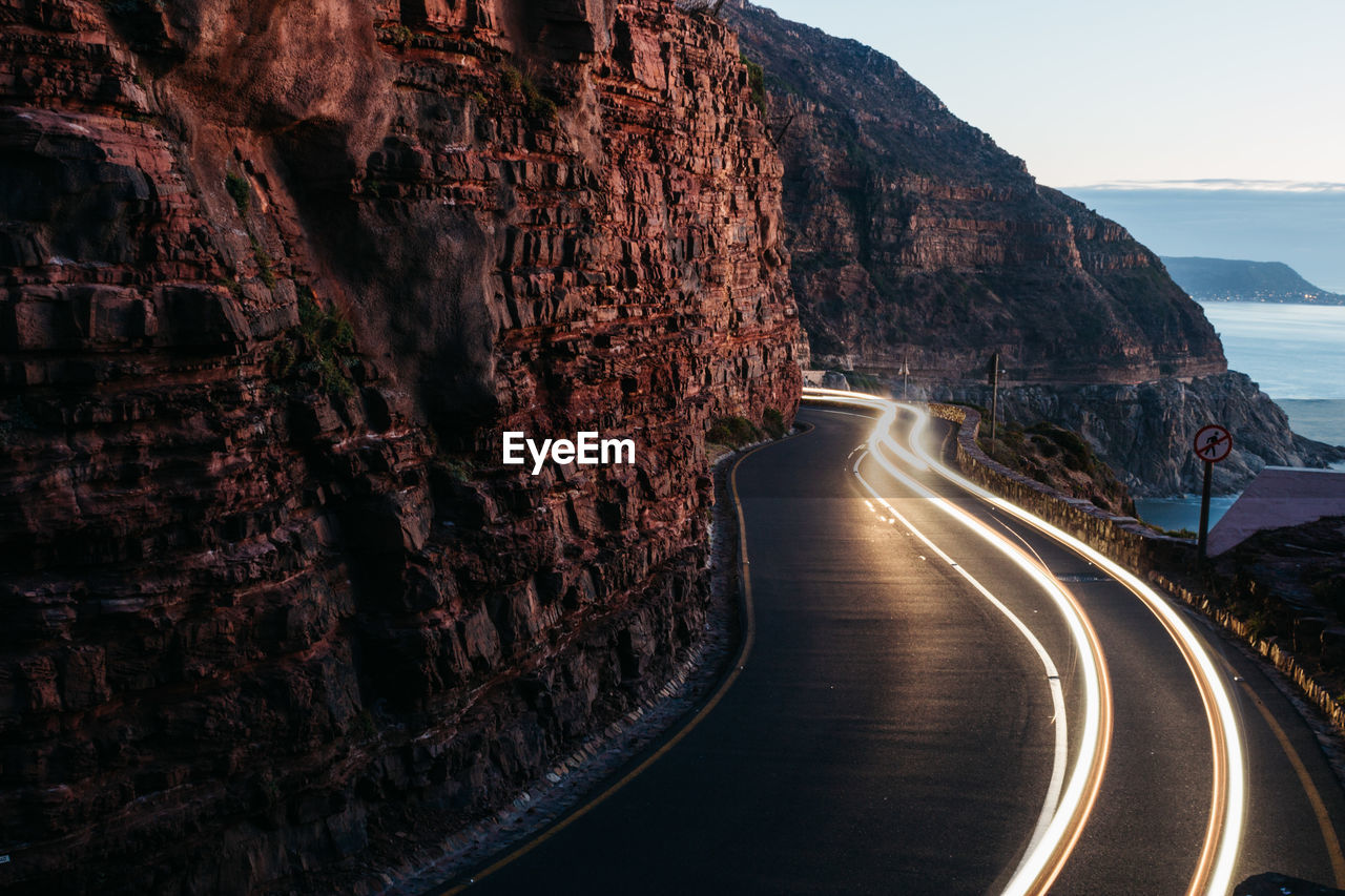 Light trails on road amidst rock formation against sky