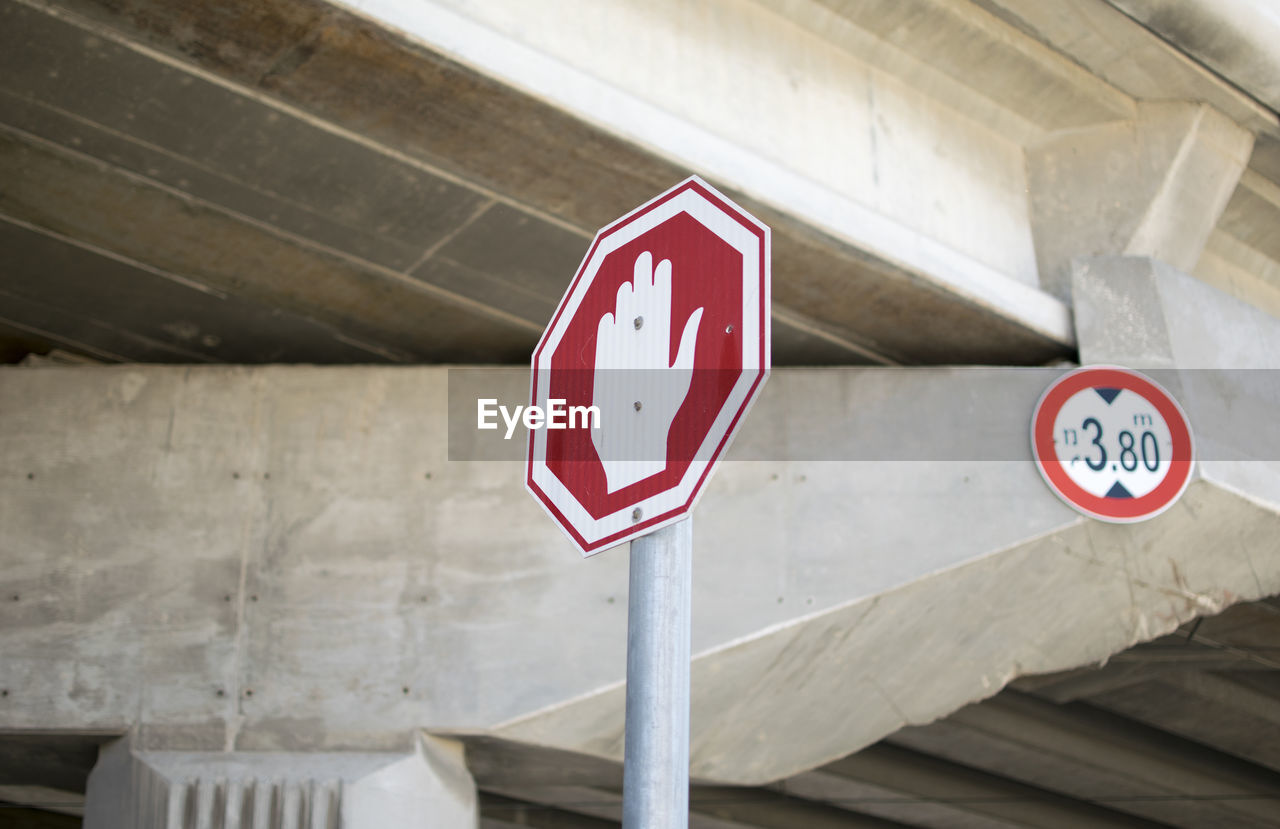 communication, sign, no people, built structure, architecture, red, warning sign, road sign, guidance, information sign, focus on foreground, day, shape, information, road, close-up, geometric shape, symbol, circle, arrow symbol, architectural column