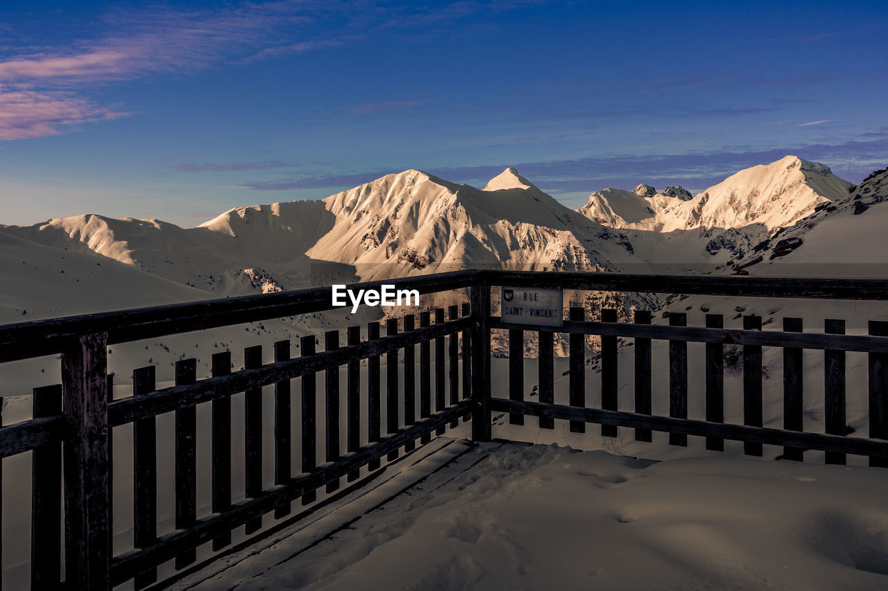 BUILT STRUCTURE ON SNOWCAPPED MOUNTAINS AGAINST SKY