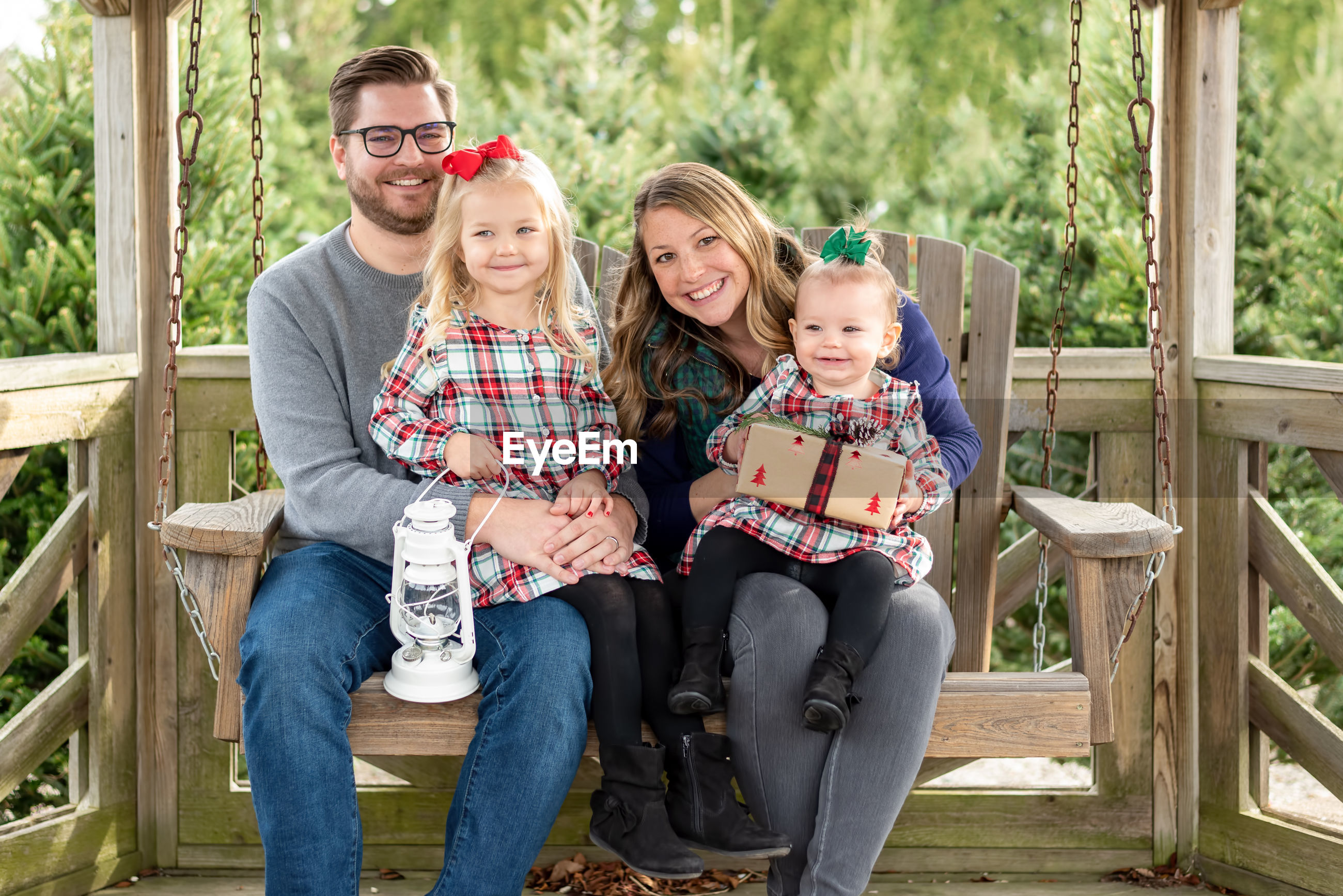 Full length portrait of cheerful family sitting outdoors