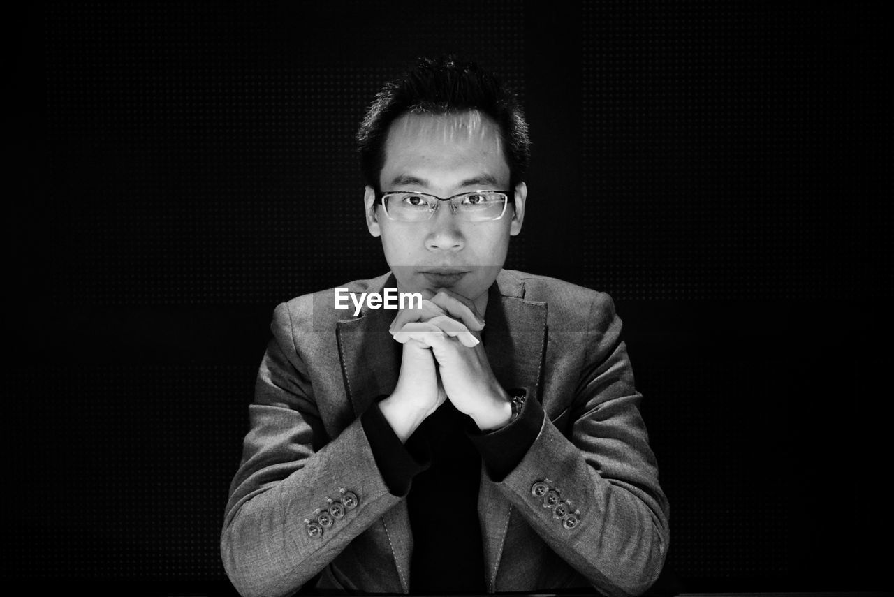 Portrait of young man with hands clasped against black background