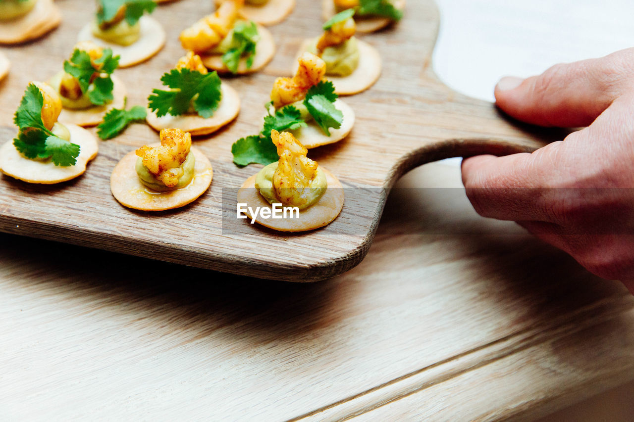 Cropped Hand Of Person With Food On Serving Board