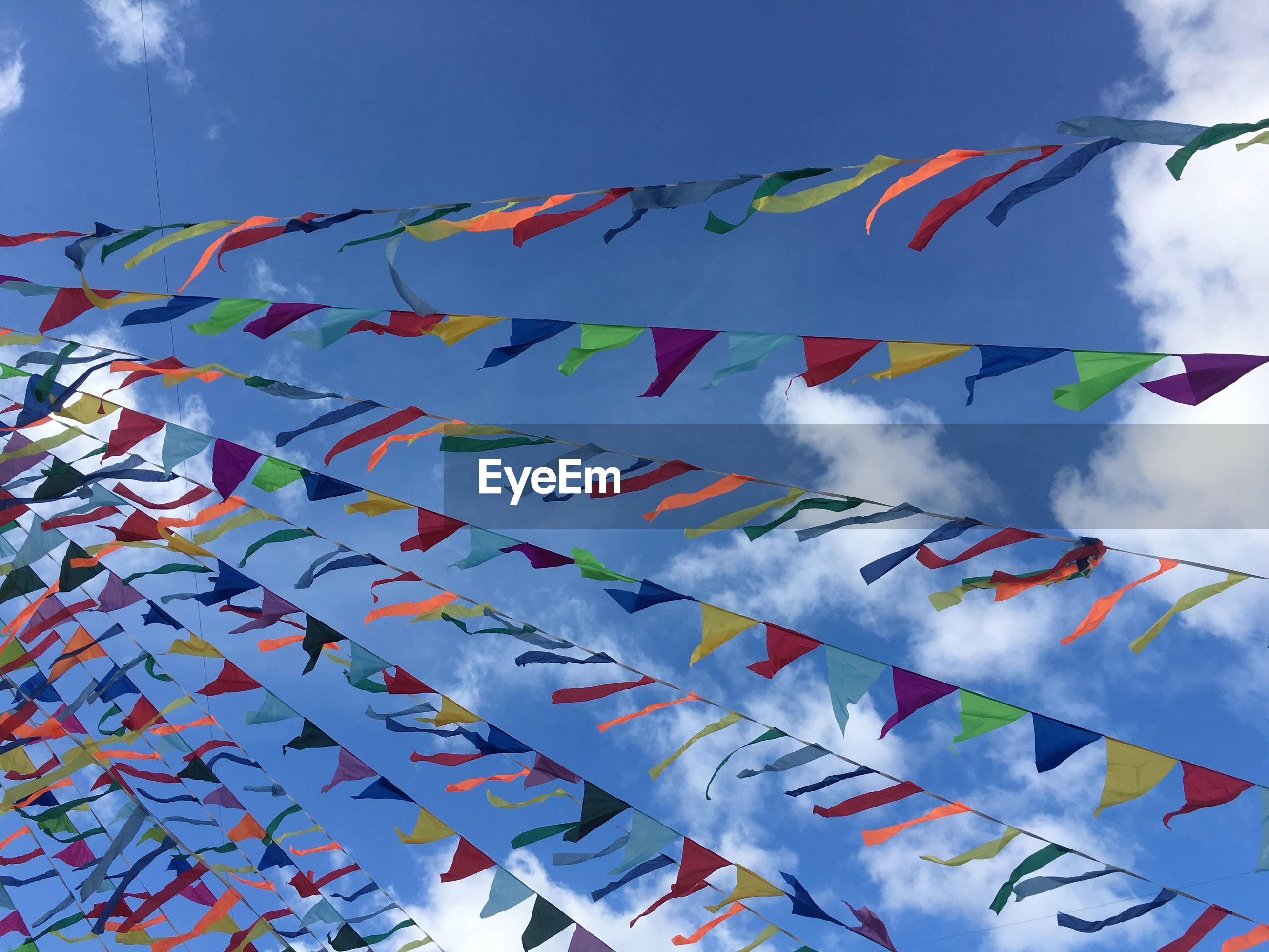 Low angle view of buntings hanging against blue sky