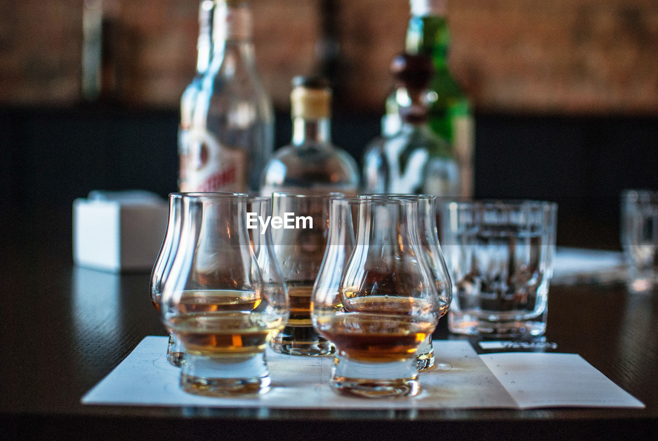 Close-Up Of Whiskey Glasses And Bottles On Table In Bar