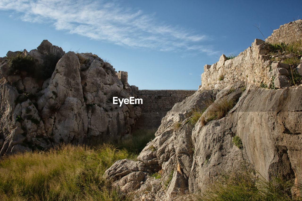 rock, sky, rock - object, solid, rock formation, land, nature, mountain, cliff, tranquility, beauty in nature, tranquil scene, environment, plant, non-urban scene, scenics - nature, no people, day, geology, landscape, outdoors, formation, eroded