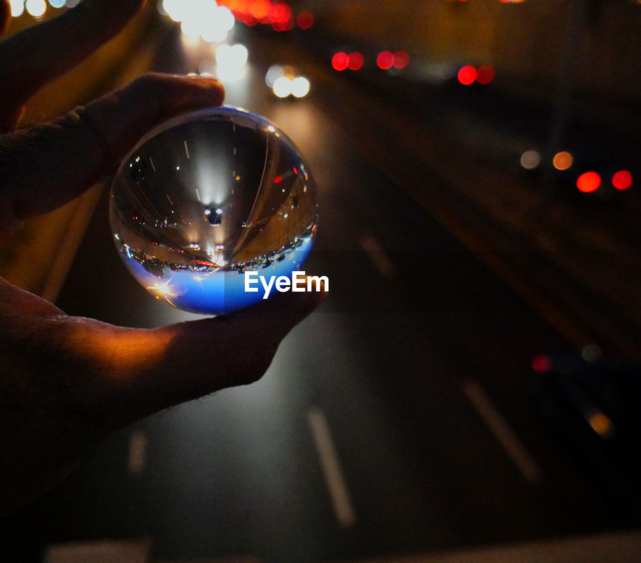 Cropped hand holding crystal ball against road at night