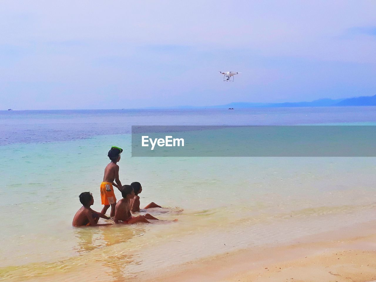 sea, horizon over water, real people, beach, water, sky, leisure activity, shirtless, nature, men, togetherness, beauty in nature, scenics, boys, vacations, lifestyles, day, outdoors, mid-air, father, childhood, two people, sand, flying, bonding, friendship, young adult, people