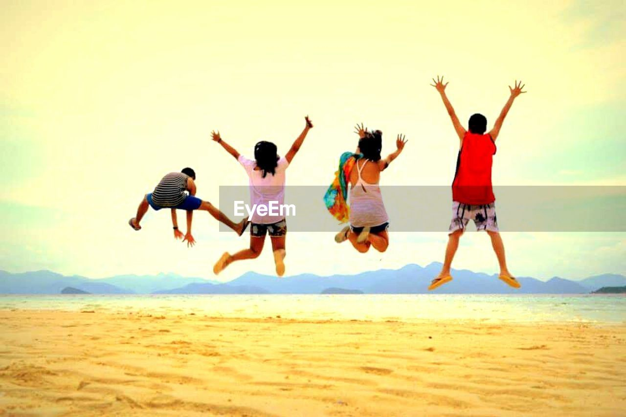 sand, arms raised, limb, human arm, fun, jumping, mid-air, full length, beach, vacations, freedom, human body part, togetherness, friendship, summer, enjoyment, joy, motion, sea, rear view, outdoors, sky, happiness, people, day, child, flying, children only, real people, nature, adult, energetic, young adult