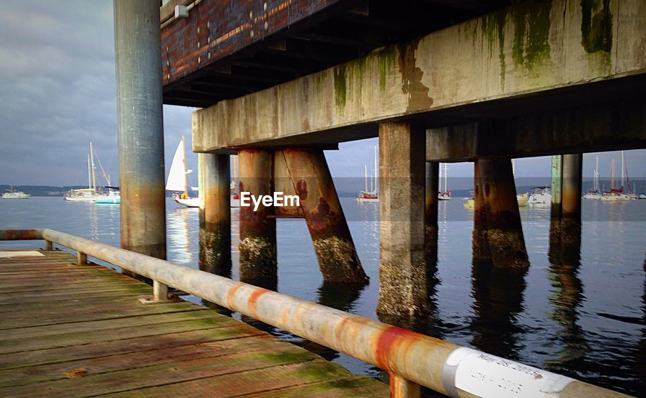 bridge - man made structure, pier, underneath, water, connection, architecture, below, river, built structure, wood - material, architectural column, bridge, day, nature, under, outdoors, no people, covered bridge, sky