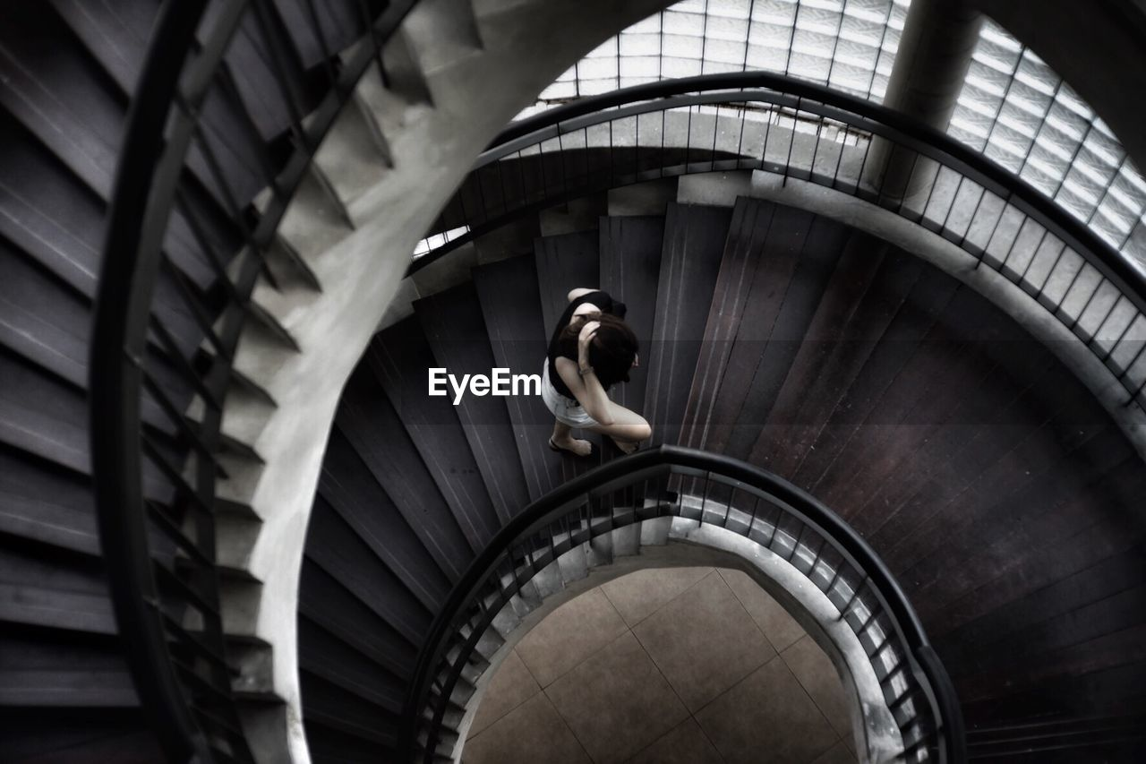 High Angle View Of Woman Walking On Spiral Staircase