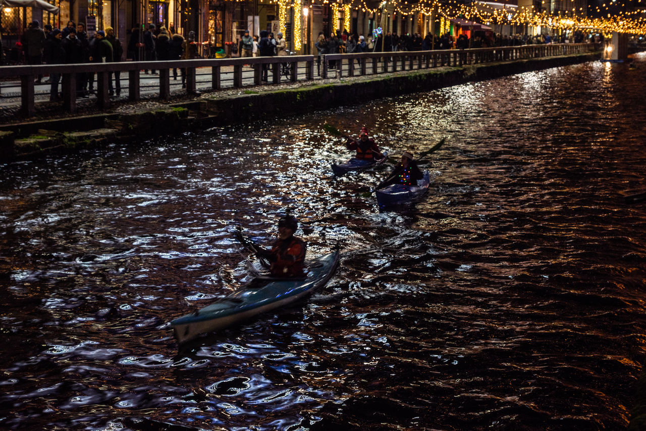 water, waterfront, river, nautical vessel, nature, transportation, real people, men, people, leisure activity, lifestyles, high angle view, mode of transportation, group of people, outdoors, rippled, day, architecture