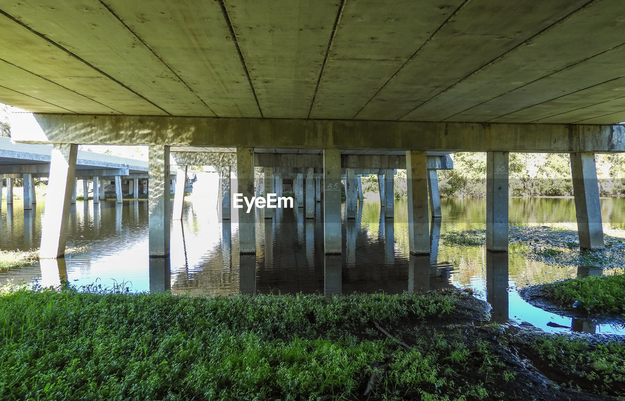 architecture, built structure, water, plant, day, no people, nature, bridge, architectural column, bridge - man made structure, reflection, connection, growth, grass, outdoors, river, underneath, ceiling, roof beam