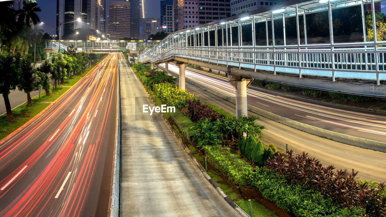 architecture, road, built structure, transportation, city, motion, modern, speed, traffic, illuminated, long exposure, building exterior, light trail, night, bridge - man made structure, no people, outdoors, skyscraper, tree