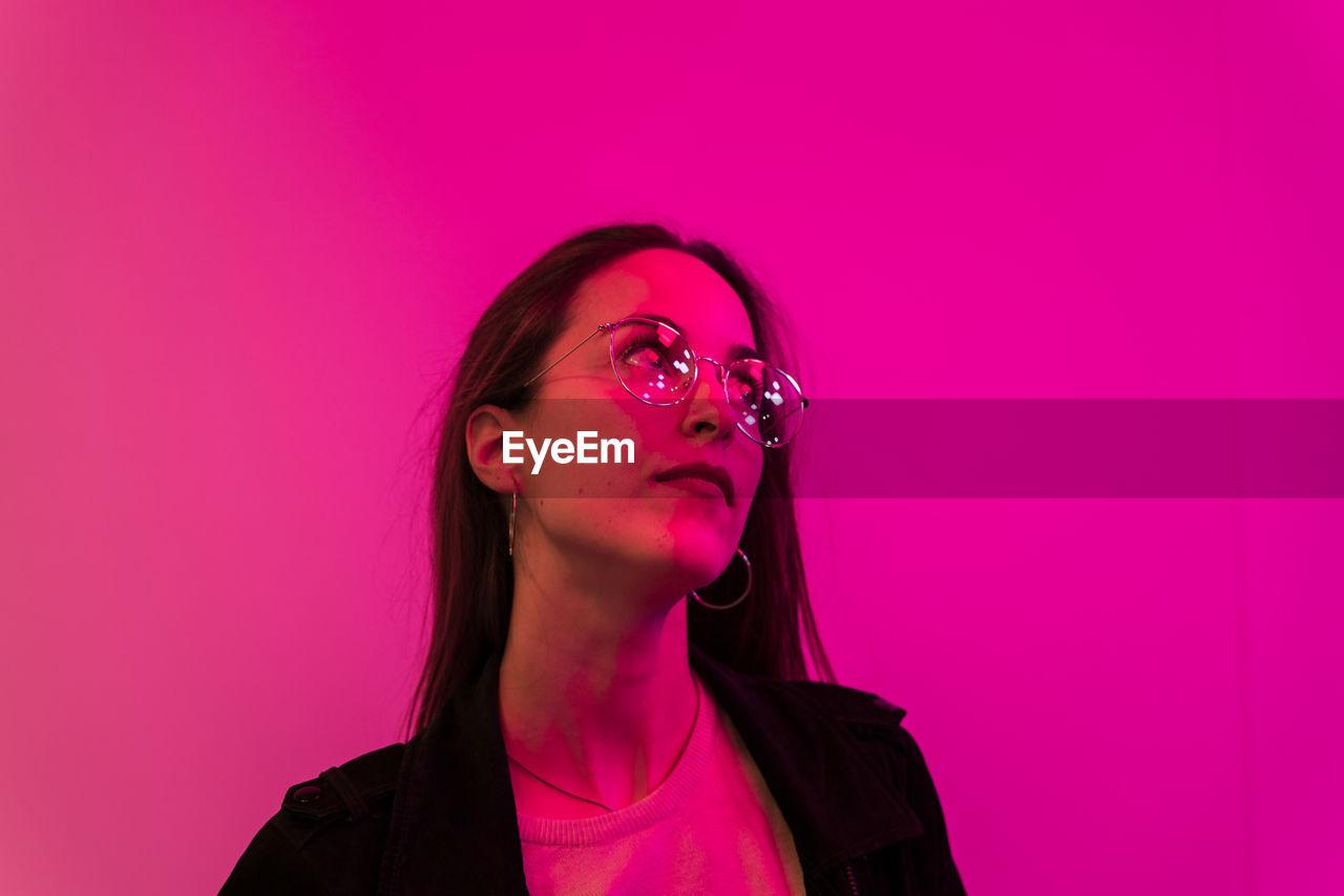 Beautiful woman in eyeglasses against pink background