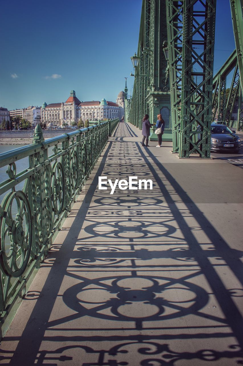 built structure, architecture, real people, one person, transportation, the way forward, sky, bridge, lifestyles, connection, direction, nature, bridge - man made structure, day, full length, shadow, sunlight, railing, walking, building exterior, diminishing perspective, outdoors, footbridge