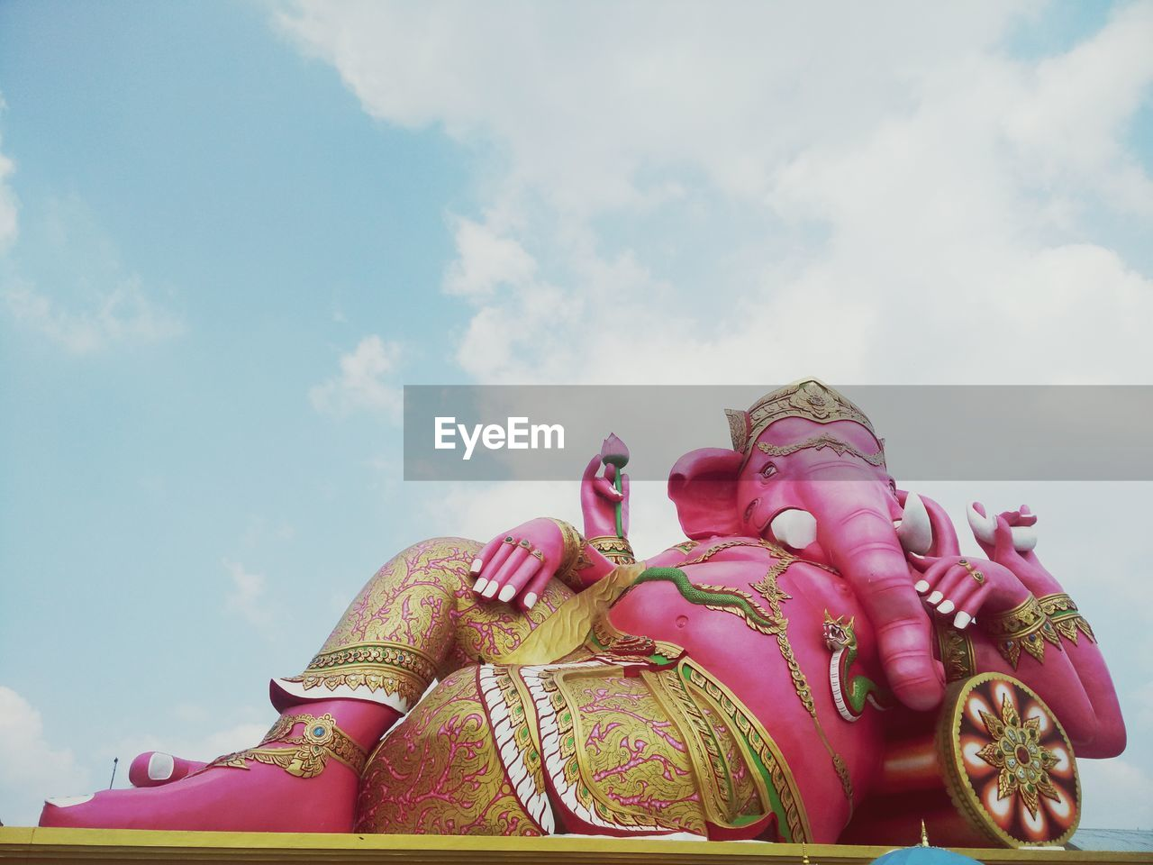 sky, cloud - sky, low angle view, art and craft, statue, sculpture, no people, religion, outdoors, day, spirituality, multi colored, carousel