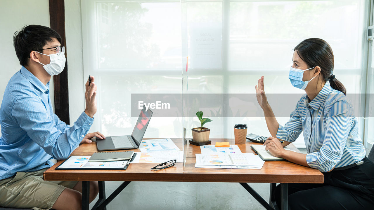 Male and female entrepreneur discussing through glass shield at office