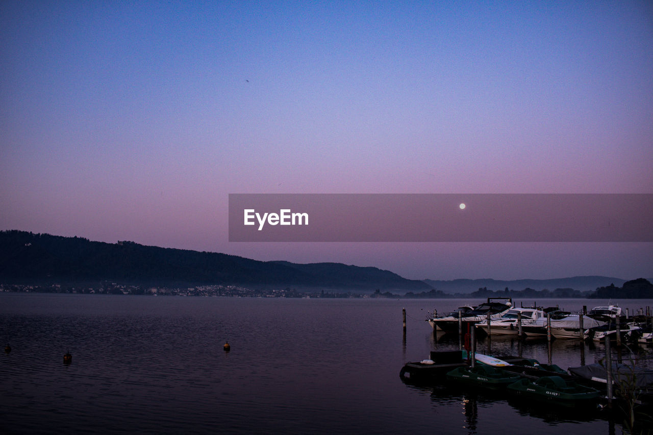 water, sky, scenics - nature, beauty in nature, tranquility, tranquil scene, nautical vessel, moon, lake, sunset, waterfront, transportation, copy space, nature, clear sky, no people, idyllic, mountain, outdoors, bay