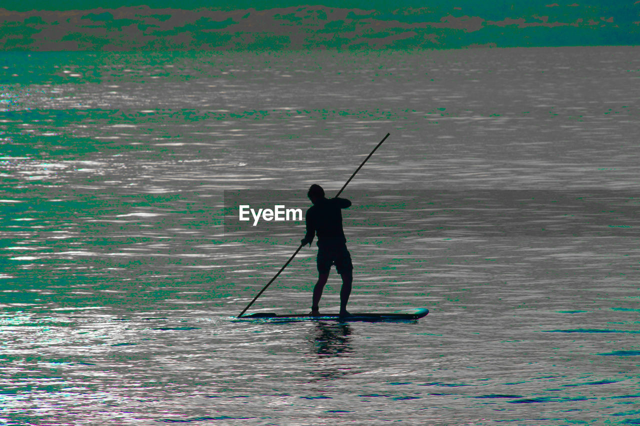 standing, one person, nature, holding, fishing, leisure activity, full length, real people, silhouette, sport, adventure, water, sea, men, day, outdoors, oar, fishing pole, beauty in nature, horizon over water, paddleboarding, adult, people