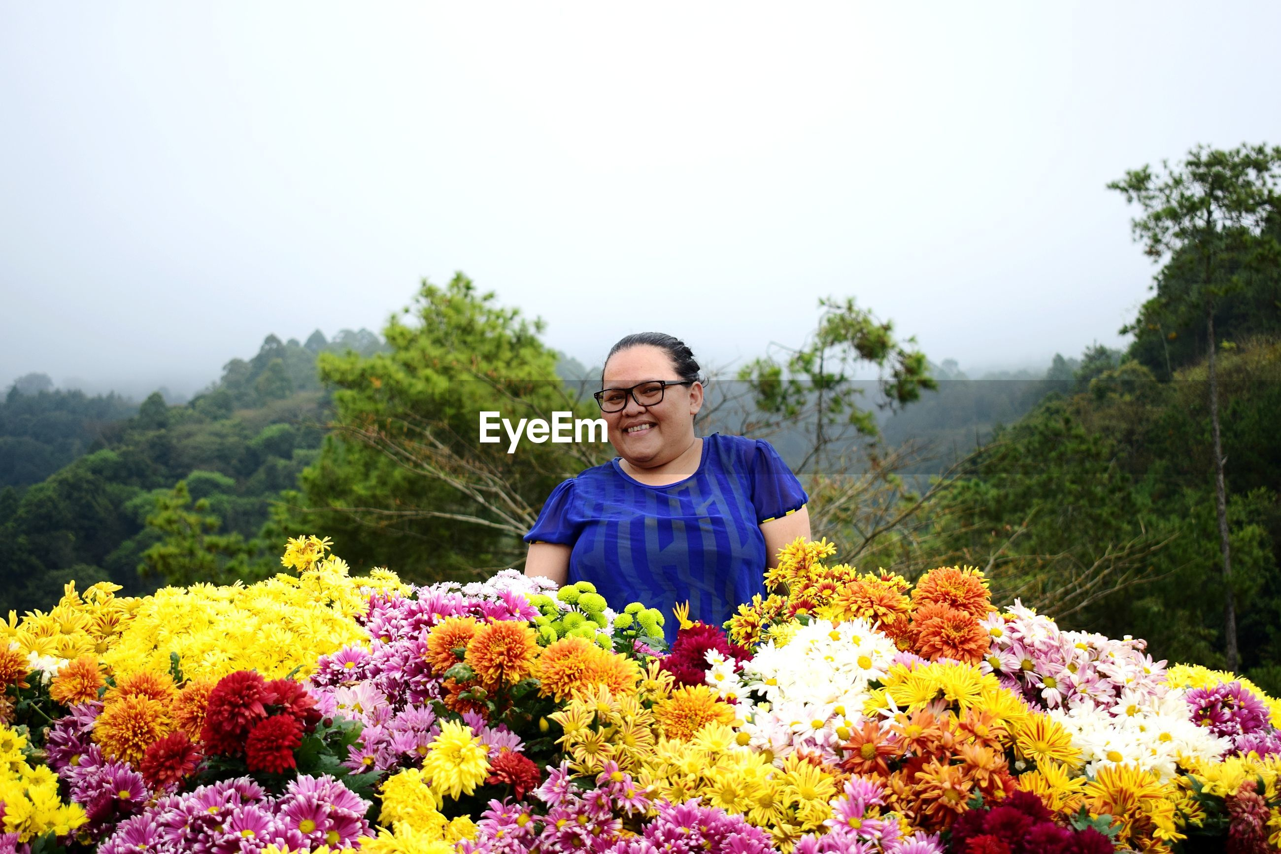 Portrait of smiling woman with various flowers against sky