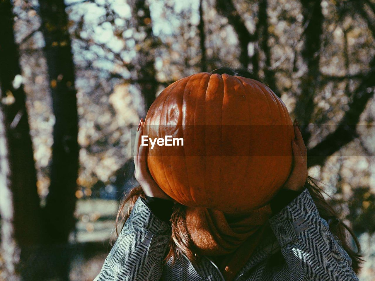 Teenage Girl Covering Face With Pumpkin