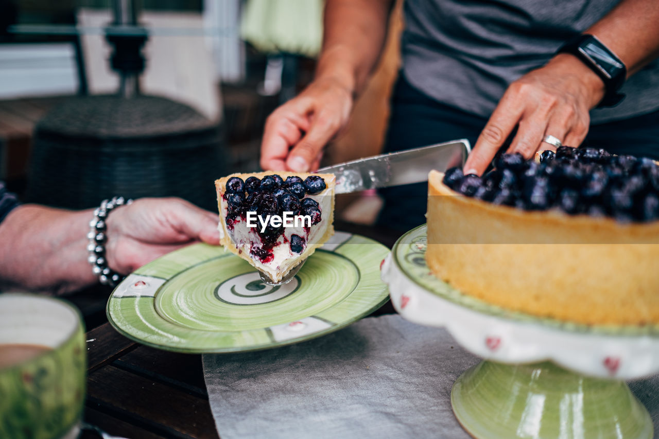 Midsection of woman preparing cake on table