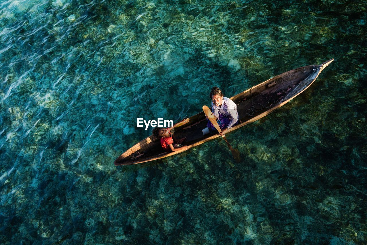 High Angle View Of Mother And Son Sailing Boat On Sea