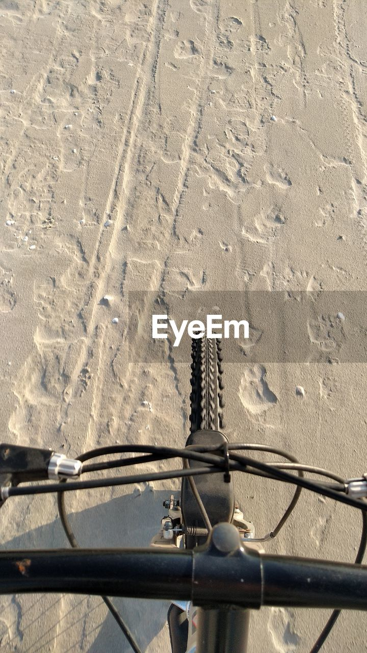 bicycle, nature, day, sunlight, land, high angle view, transportation, sand, shadow, no people, land vehicle, mode of transportation, outdoors, metal, beach, sunny, road, handlebar, connection, pattern, wheel