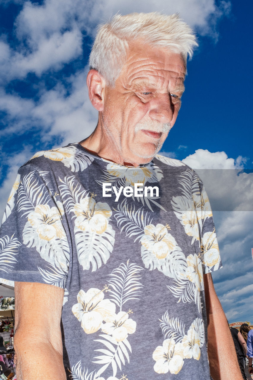 real people, senior adult, cloud - sky, sky, lifestyles, one person, leisure activity, day, front view, adult, waist up, nature, casual clothing, men, males, senior men, standing, senior women, outdoors, white hair, floral pattern