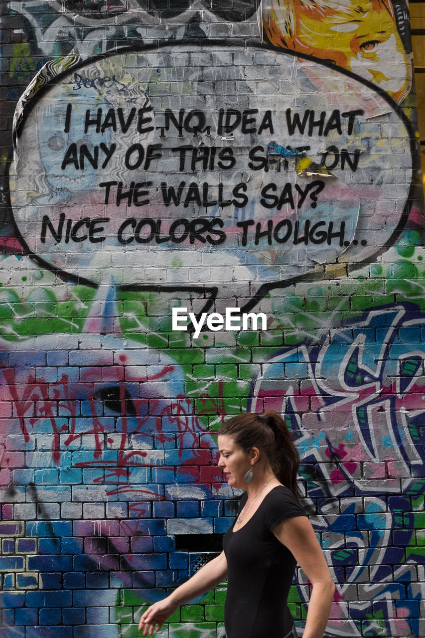 graffiti, text, multi colored, street art, communication, one person, day, lifestyles, built structure, outdoors, young adult, adult, people, adults only