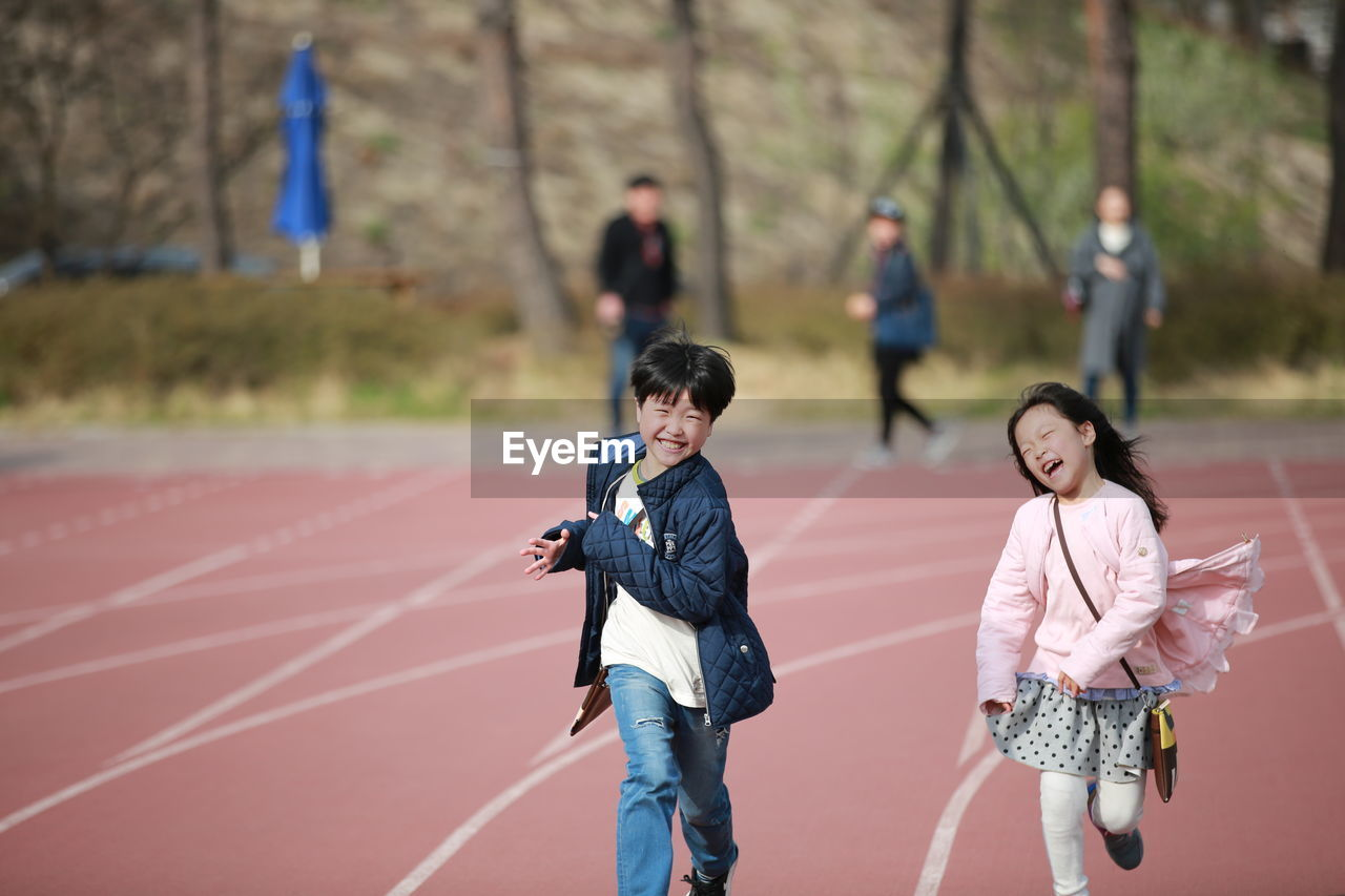 Cheerful Friends Running On Track