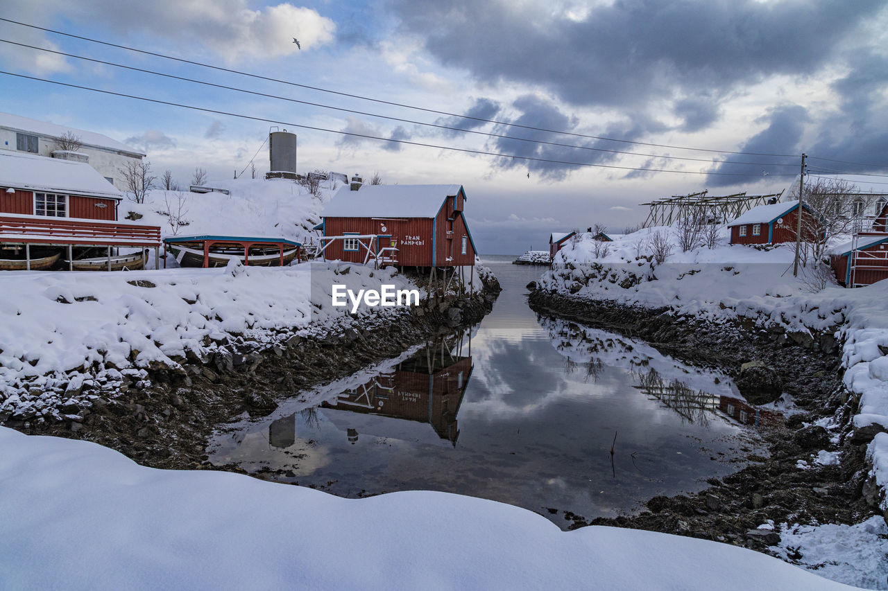 SNOW COVERED HOUSES AGAINST SKY