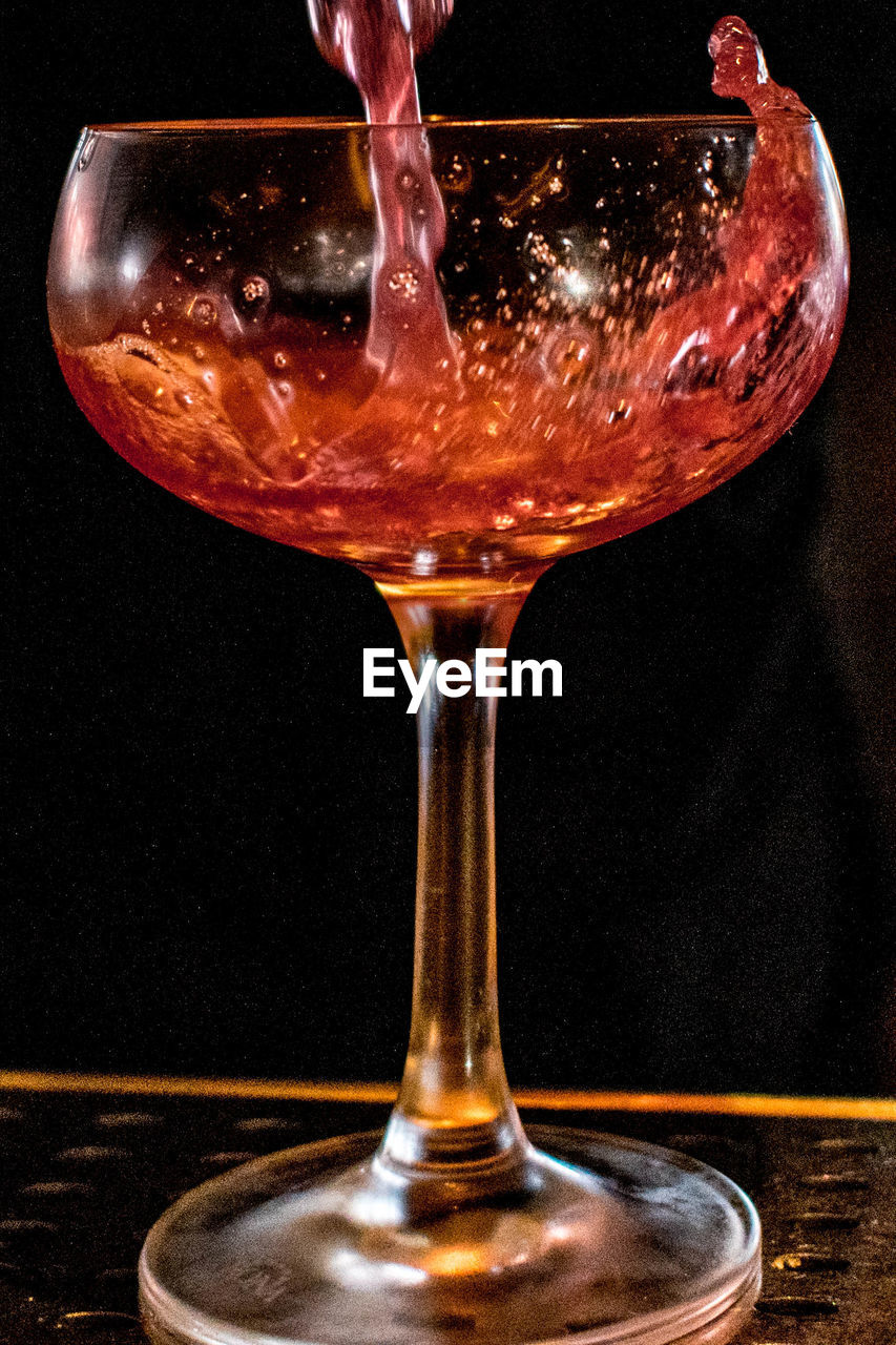 Close-Up Of Alcoholic Drink Being Poured In Drinking Glass On Table